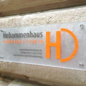 Folierung eines Acrylglasschildes, auf Sandstein montiert