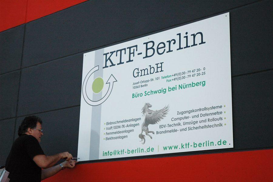 Großes Alu Dibond Schild während der Montage an Fassade