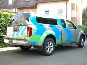 Auffällig beklebtes Fahrzeug mit blauen und grünen Elementen