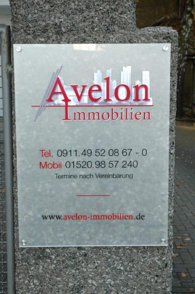 An Stein montiertes Plexiglasschild für Avelon Immobilien