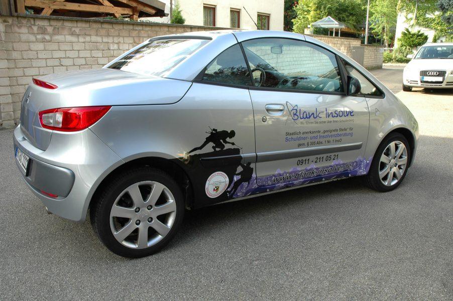 Seitenansicht eines silbernen Autos mit neuer Fahrzeugbeklebung