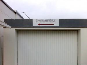 Anbringung eines Schildes an Garage mit Wegweiser