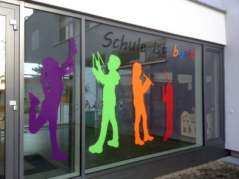 Lila, grüne, orangene und rote Schattenfigur von Schulkindern in unterschiedlichen Posen zur Verschönerung eines Schuleingangs