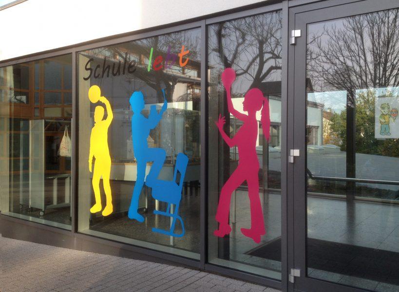 Gelbe, blaue und pinke Schattenfigur von Schulkindern in unterschiedlichen Posen zur Verschönerung eines Schuleingangs