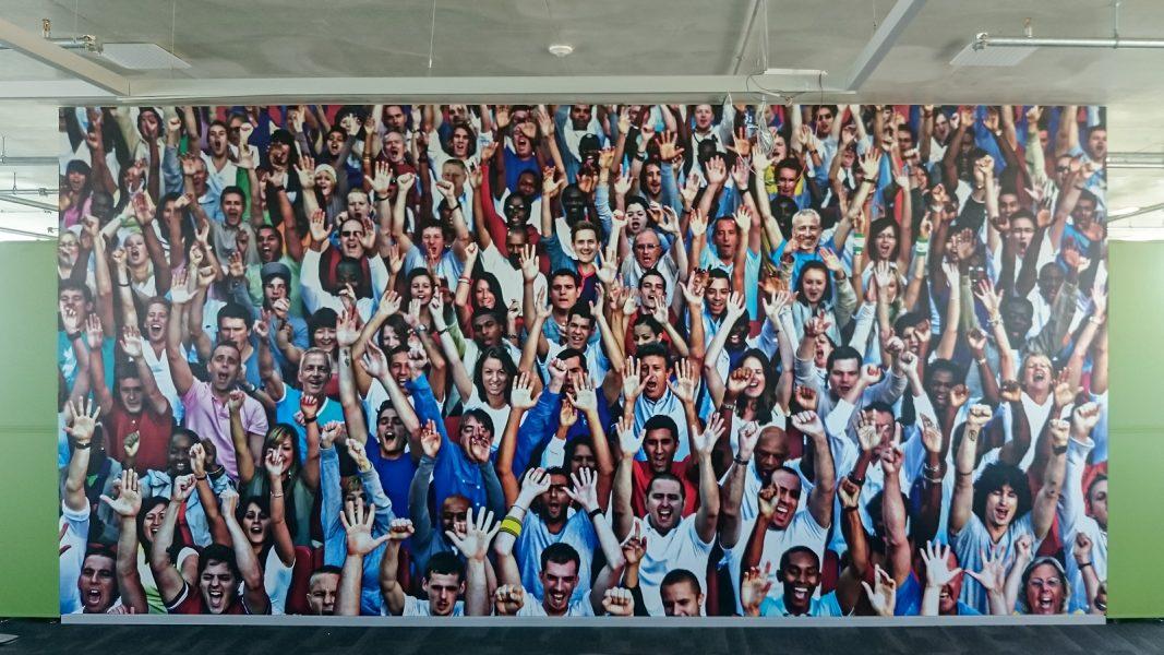Beklebung eines großflächigen Wandtattoos mit jubelnden Menschen
