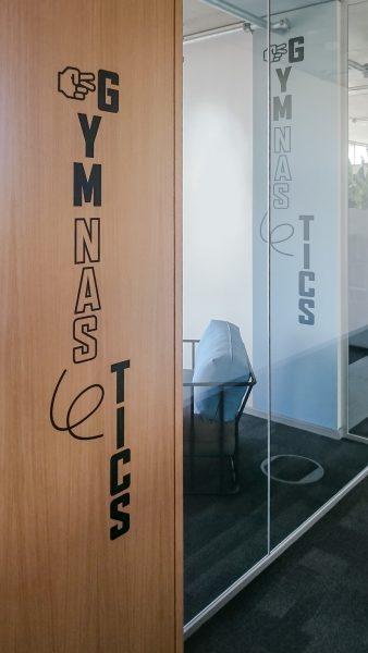 "Folierung des Schriftzuges ""Gymanstics"" an einer Bürotüre"