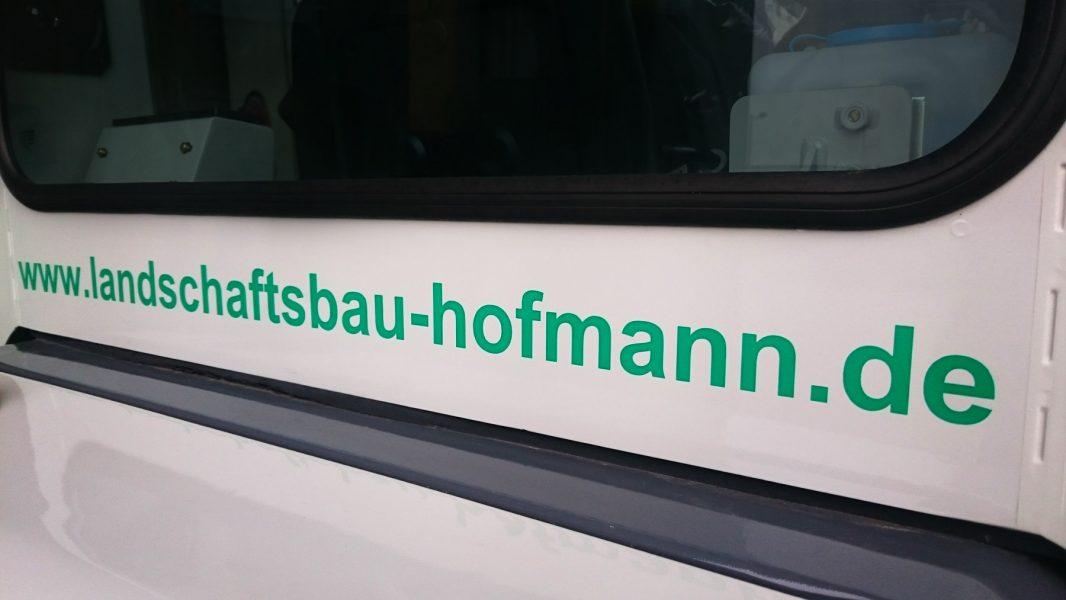 Detailaufnahme des beklebten Minibaggers vom Gartenbau Hofmann