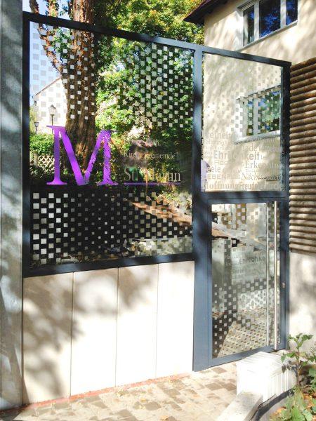 Moderne Beklebung eines Kircheneinganges mit Glasdekormuster und lila farbenem M