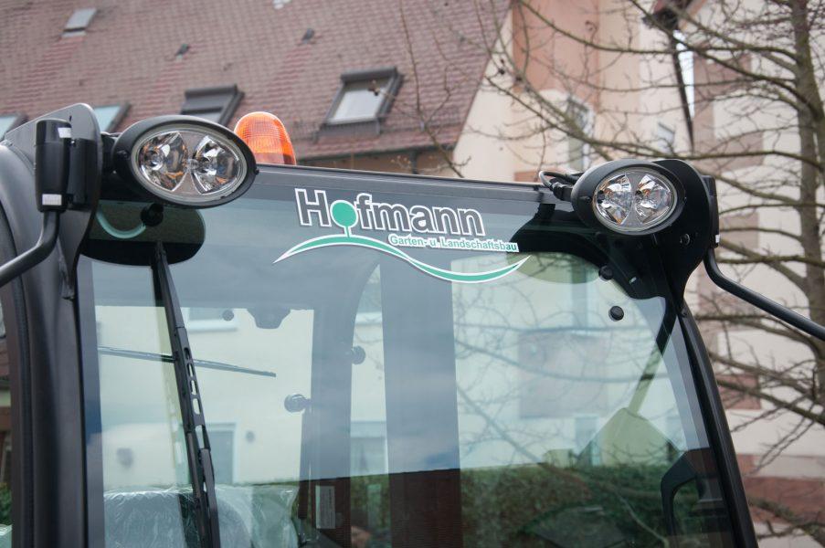 Frontscheibe des Radladers von Hofmann Garten und Landschaftsbau mit dem Logo beklebt