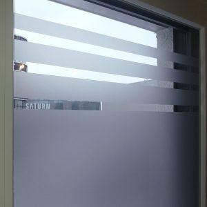 Nahaufnahme einer mit Glasdekor folierten Fensterscheibe mit 3 Abschlussstreifen