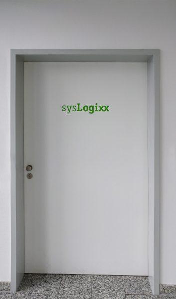 Grünes sysLogixx Logo auf weißer Holztüre