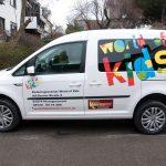 Beklebter weißer VW Caddy mit dem bunten world of kids schriftzug