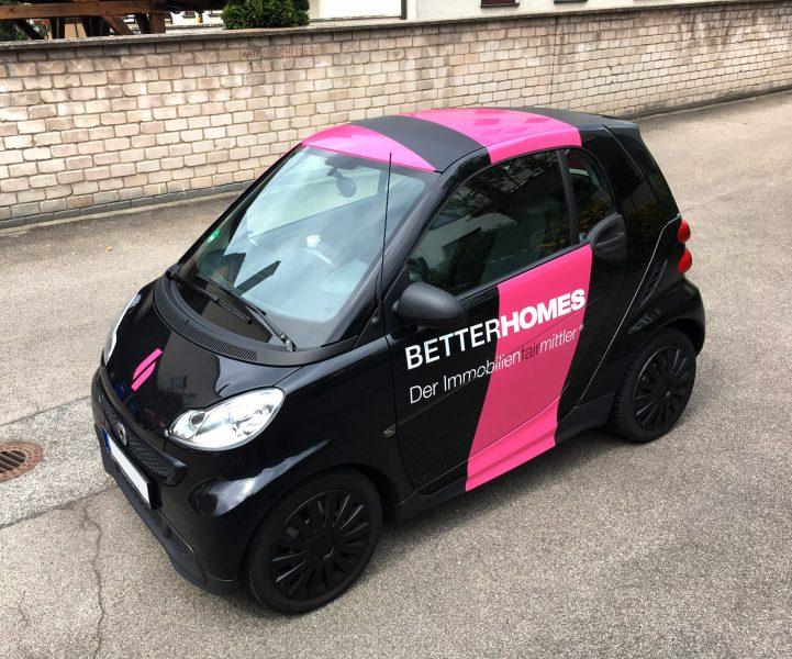 Auffällige Smartbeklebunt in Pink und Weiß auf einem schwarzen Fahrzeug