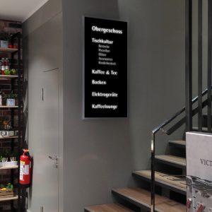 LED-Leuchtpanel an einem Treppenaufgang. Schwarz foliert mit ausgeschnittenem Schriftzug, der weiß leuchtet.