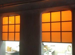 Plexiglasschilder mit orangfarbener Folie über einer Durchreiche