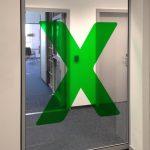 """Transluzente Folierung eines großen grünen """"X"""" auf Glasscheibe"""