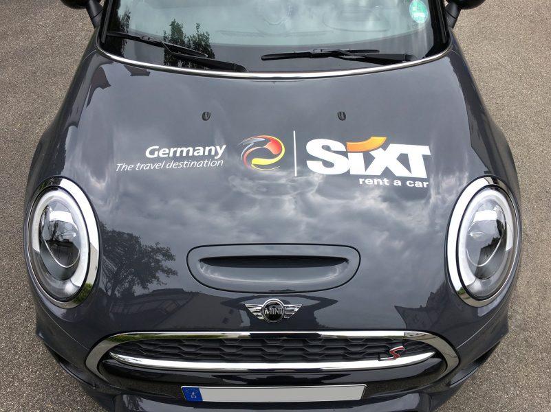 Großflächige Beklebung des Sixt Logos auf schwarzer Motorhaube