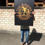 Foliertes Blechschild in schwarz matt mit gelbem Singing Bar Keepers Logo