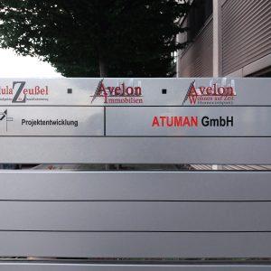 Minimalistische Firmenbeklebung an Schildanlage aus Edelstahl