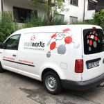 Schrägansicht eines mailworXs Fahrzeuges mit Vernetzungsgrafik und Logo in 3 Farben