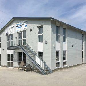 Schrägansicht der Lagerhalle mit 2 großen Alu Dibond Schildern an der Fassade