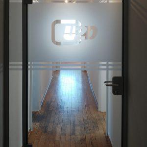 Glasdekordesign als Sichtschutz mit negativ herausgeschnittenem Logo und Abschlusstreifen oben und unten