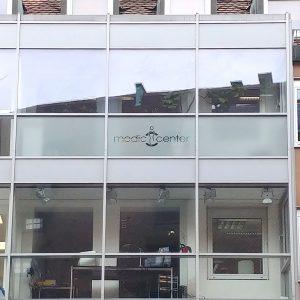 Folierung einer Fensterreihe mit Glasdekorflächen und Flächen mit negativ herausgeschnittenem Logo