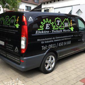 Gesamtansicht einer Fahrzeugbeklebung. Ein schwarzes Fahrzeug wurde mit leuchten grüner und grauer Folie foliert.