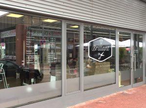 Frontansicht eines folierten Friseursalons mit Glasdekorfolie, Preisliste und Logo