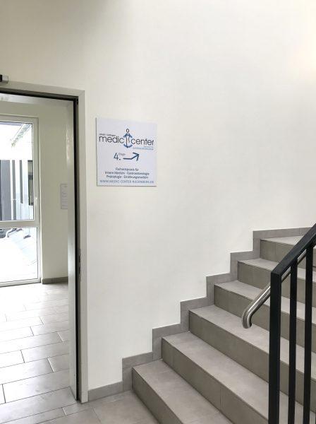 Anbringung eines folierten Schildes in einem Treppenhausaufgang