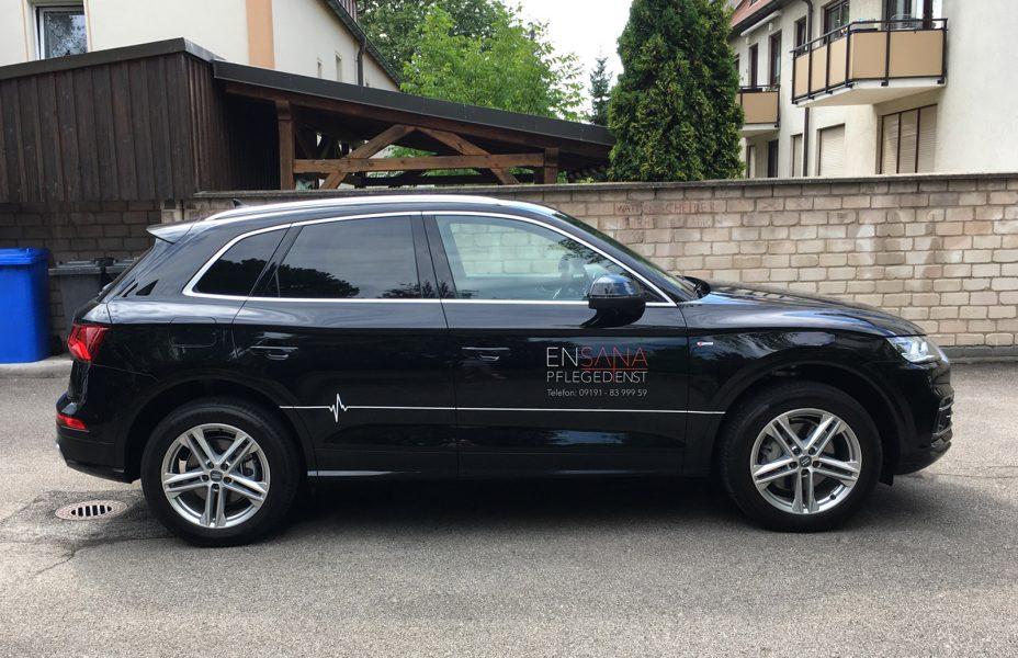 Seitenansicht der filigranen Fahrzeugbeklebung eines schwarzen Audis mit weißer und roter Folie