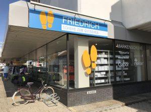 Großes Schild für das Schuhgeschäft Friedrich über dem Schaufenster des Ladens. Zudem sieht man darunter die Folienbeschrifteten Schaufenster