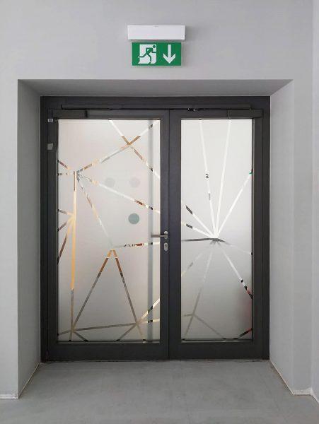 Netzgrafik aus Glasdekor als Sicht- und Durchlaufschutz auf einer Eingangstüre bei Design Offices