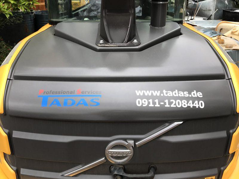 Beklebungsarbeiten - Heckfolierung eines Baggers mit Logo für Tadas