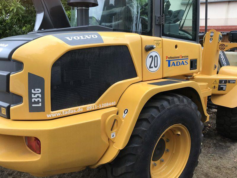 Beklebungsarbeiten - Schrägansicht eines gelben Baggers mit Folienbeschriftung für die Firma Tadas