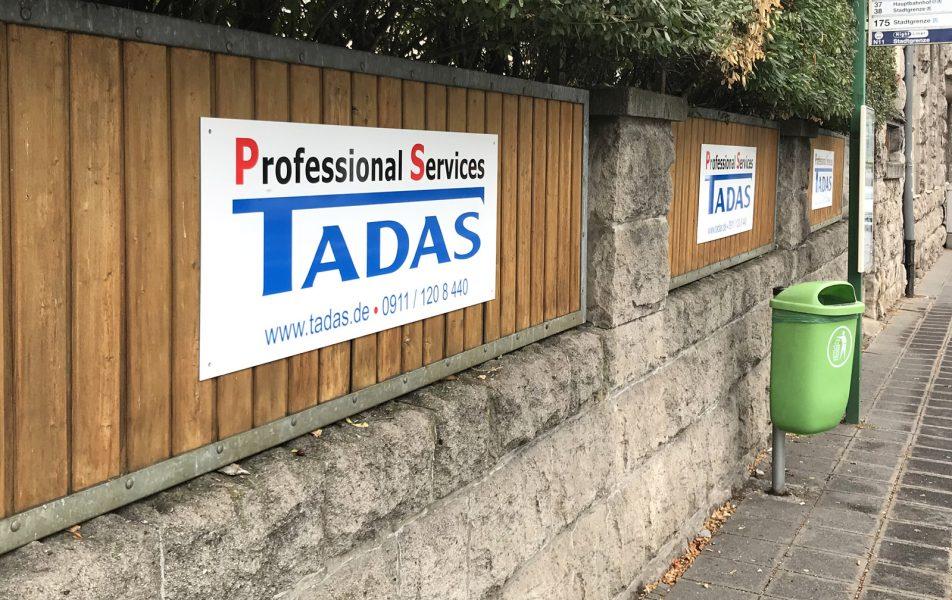 Beklebungsarbeiten - Drei Schilder, die an einen Holzzaun montiert wurden und alle mit dem Tadas Logo foliert sind