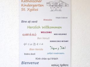 Schild auf weißer Hausfassade für den Katholischen Kindergarten St. Xystus