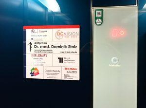 Aufkleber mit den abgebildeten Firmen in den einzelnen Stockwerken, der an der Wand in einem Aufzug befestigt wurde