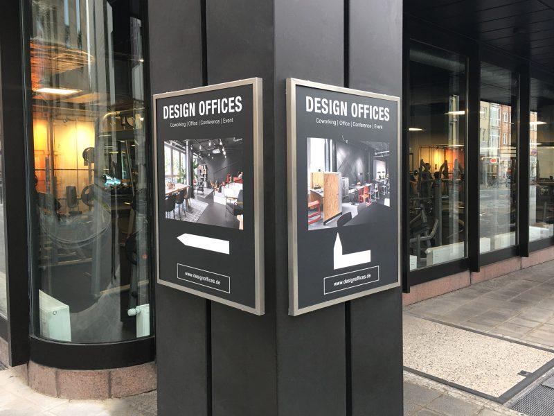 Matt gedruckte Poster in einem Werberahmen für Design Offices, dass an einem breiten Pfosten montiert ist.