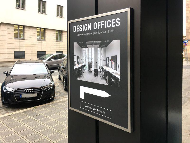 Matt gedrucktes Poster in einem Werberahmen für Design Offices, dass an einem breiten Pfosten montiert ist.