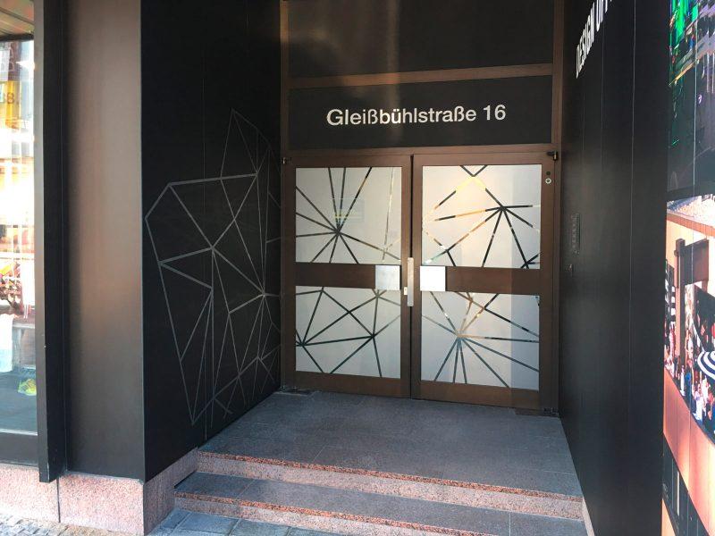 Blick auf den Eingangsbereich von Design Offices in Nürnberg. Man sieht die mit schwarzmattfolie beklebte Gebäudewand. Darauf wurde ein Gitternetz aus Glasdekor angebracht.