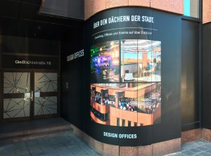 Schilder und Beklebung - Blick auf den Eingangsbereich von Design Offices in Nürnberg. Man sieht eine abgerundetes Hauseck,, dass vollflächig mit digital bedruckter Folie beklebt wurde