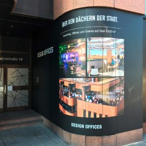 Blick auf den Eingangsbereich von Design Offices in Nürnberg. Man sieht eine abgerundetes Hauseck,, dass vollflächig mit digital bedruckter Folie beklebt wurde