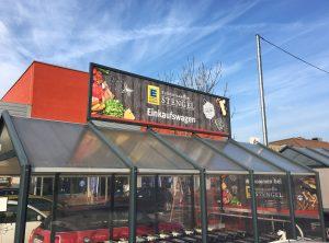 Beklebungsarbeiten - Großes Schild über dem Park-Stellplatz für die Einkaufswagen bei Edeka Stengel