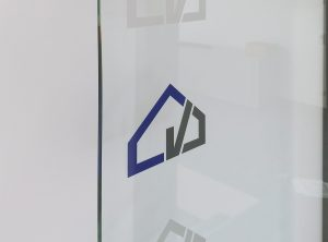 Türfolierung - Detailaufnahme einer Glastürbeklebung mit dem Firmenlogo von Denner