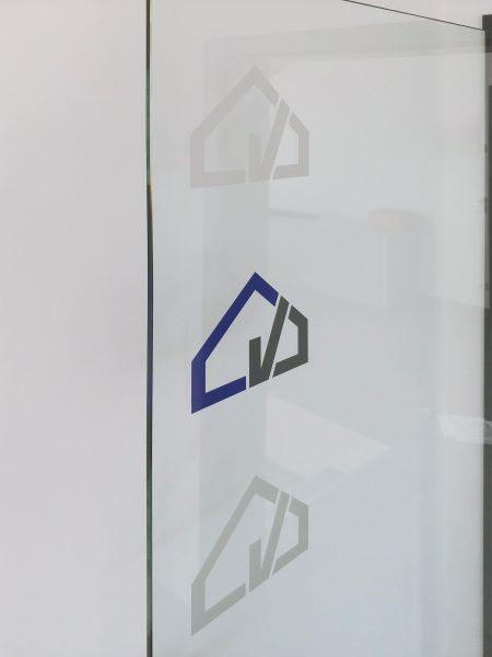 Detailaufnahme einer Glastürbeklebung mit dem Firmenlogo von Denner