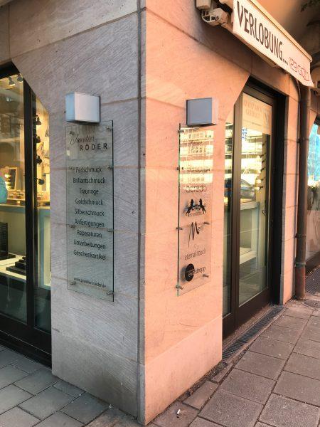Mit Marken folierte Glasscheibe, welche mit Abstandshaltern an der Sandsteinwand montiert