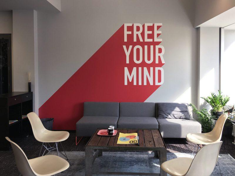 zweifarbiges Wandtattoo mit den Worten FREE YOUR MIND auf einer grauen Wand für Design Offices
