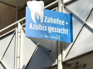 Detailansicht des montierten Nasenschildes zur Suche von Personal in einer Zahnarztpraxis