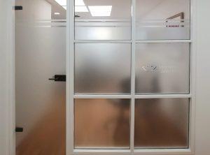 Glaswand mit Sichtschutzfolie und negativ ausgeschnittenem Logo in der Zahnarztpraxis Lücking in Adelsdorf
